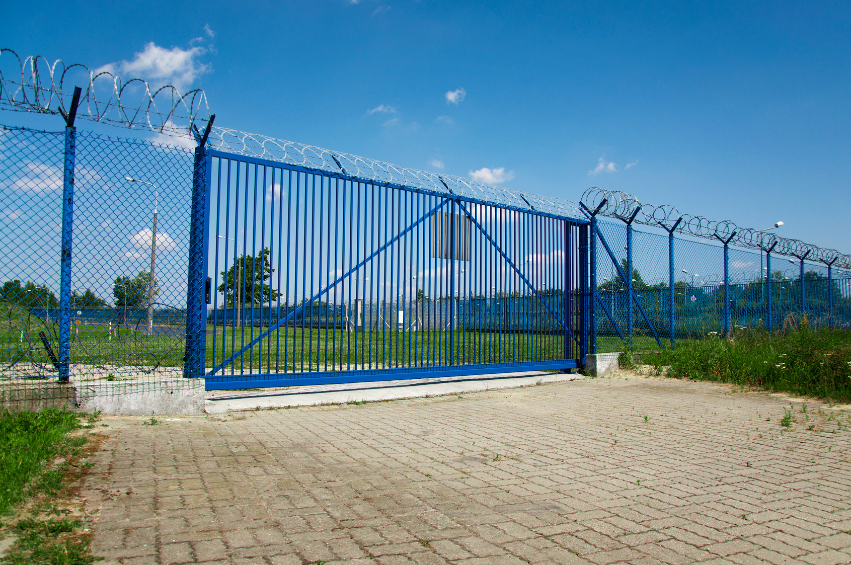 blue fence gate with barbed wire